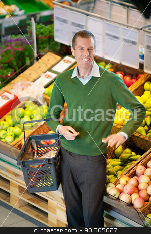 Man in Grocery Store stock photo, Mid adult man carrying shopping basket and looking at camera while shopping in fruit store by Tyler Olson
