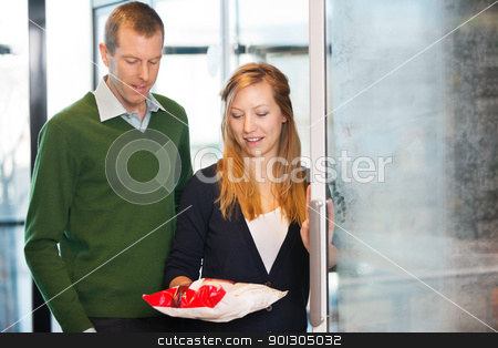 Couple Buying Frozen Food stock photo, Woman taking out product from freezer while shopping with husband by Tyler Olson