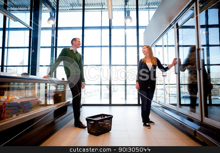 Supermarket Man Woman Flirt stock photo, A smiling couple flirting in the supermarket by Tyler Olson