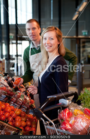 Supermarket Woman and Clerk stock photo, A woman buying fruit at a supermarket receiving help from a store clerk by Tyler Olson