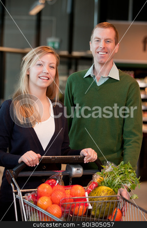 Grocery Store Couple Portrait stock photo, Portrait of a happy couple in a grocery store by Tyler Olson