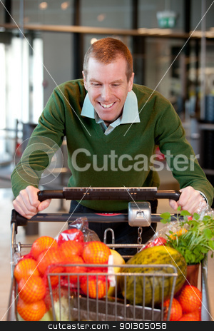 Male in Grocery Store stock photo, Portrait of a man pushing a grocery cart in a grocery store by Tyler Olson