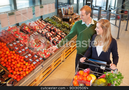 Man pointing at vegetables stock photo, Smiling mid adult man pointing at vegetables while shopping with wife in grocery store by Tyler Olson