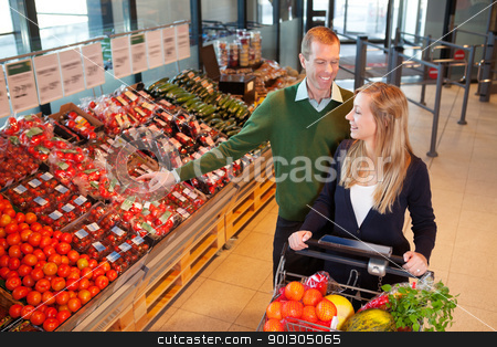 Couple Buying Fruits and Vegetables stock photo, Mid adult man pointing at vegetables while shopping with wife in shopping store by Tyler Olson