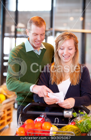 Grocer List in Supermarket stock photo, A happy couple looking at a grocery list in a supermarket by Tyler Olson