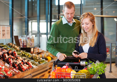Couple Buying Groceries with List on Phone stock photo, A happy couple buying groceries looking at grocery list on phone by Tyler Olson