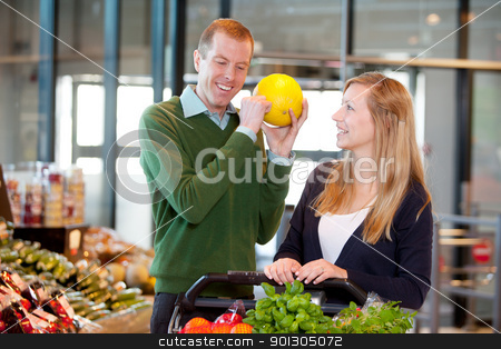 Man Checking Ripeness of Melon stock photo, A man knocking on a melon to check if it is ripe by Tyler Olson