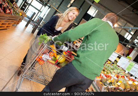 Couple in playful mood in store stock photo, Man and woman in playful mood pushing shopping cart in shopping store by Tyler Olson