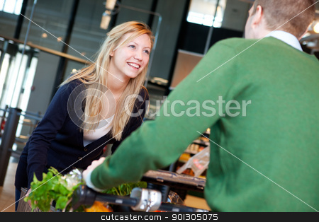 Playful Couple in Supermarket  stock photo, A man pushing a woman standing on a grocery cart by Tyler Olson
