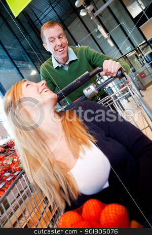 Playful Couple in Supermarket stock photo, A woman in a shopping cart - a playful crazy couple in a supermarket by Tyler Olson