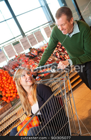 Grocery Store Playful Couple stock photo, Adult man in playful mood pushing shopping cart while woman sitting in it by Tyler Olson