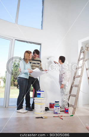 Young couple looking at blueprint stock photo, Young couple looking at blueprint while worker painting their house by Tyler Olson