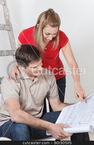 Couple with Blueprints stock photo, Couple looking at home blueprints together by Tyler Olson