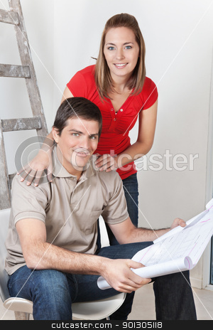 Couple with Home Blueprints stock photo, Portrait of young happy couple together with blueprints by Tyler Olson