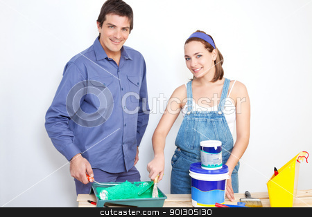 Portrait of happy couple with paint tools stock photo, Portrait of happy couple with roller, paint and bucket on table by Tyler Olson