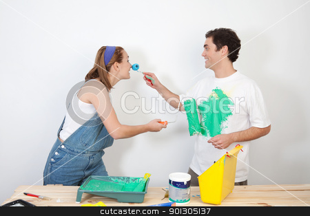 Playful couple playing with paint stock photo, Smiling man painting his wife's nose with paint by Tyler Olson