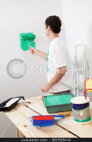 Casual man painting the wall of his new apartment stock photo, Casual man painting the wall of his new apartment with paint bucket in background by Tyler Olson
