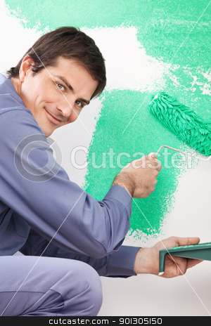 Handsome man painting house stock photo, Portrait of smiling handsome man painting his house with roller by Tyler Olson