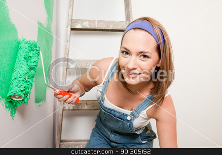 Woman Painting stock photo, A woman with a paint roller, painting a home interior by Tyler Olson