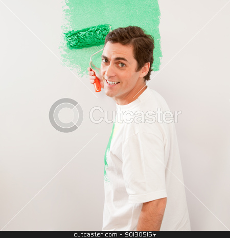 Man Painting Wall stock photo, A man paiting a wall with a roller brush by Tyler Olson