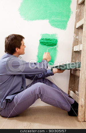 Professional Painter stock photo, A professional painter painting with a large roller brush by Tyler Olson
