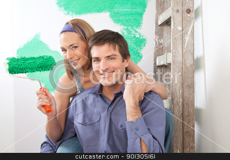 Home Improvement Painting stock photo, Beautiful young couple sitting together with color roller at home by Tyler Olson