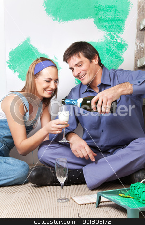 Smiling couple having champagne stock photo, Smiling man pouring champagne in woman's glass by Tyler Olson