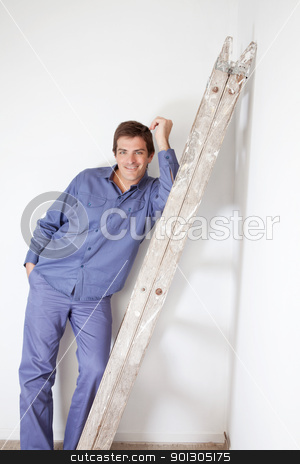 Smiling man leaning on ladder stock photo, Young man leaning on wooden ladder and smiling by Tyler Olson