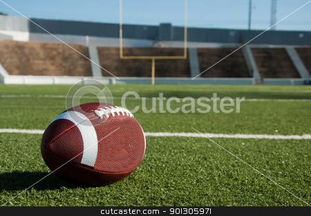 American Football on Field stock photo, American football on field with goal post in background. by Danny Hooks