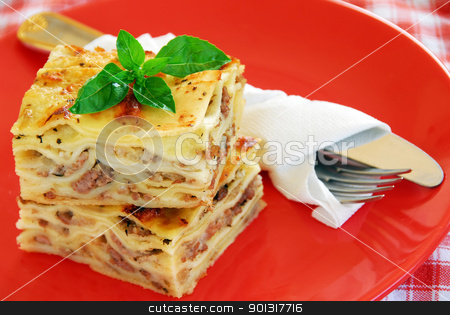 Lasagna stock photo, appetizing lasagna piece with basil on red plate by Julija Sapic