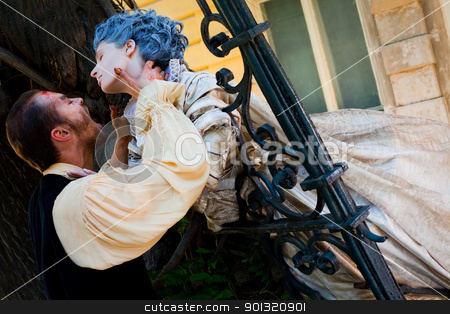 Male vampire attacking woman stock photo, Male vampire holding woman's neck, both dressed in medieval costumes by vilevi