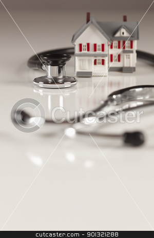 Stethoscope with Small Model Home stock photo, Stethoscope and Model House on Gradated Background with Selective Focus. by Andy Dean