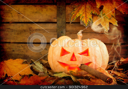 Halloween creepy pumpkin smoking cigar stock photo, Heavy textured creepy carved pumpkin face smoking a cigar on wooden bacground and autumn leafs  by borojoint