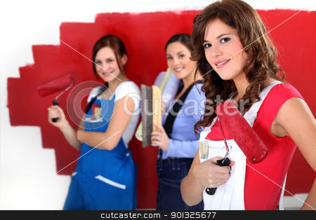 Three women painting a wall in red. stock photo, Three women painting a wall in red. by photography33