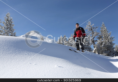 Male skier on a ski slope stock photo, Male skier on a ski slope by photography33