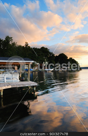 Lake sunrise stock photo, Lake house with pier and woods with sunrise in the morning in New York state Finger Lakes by rabbit75_cut