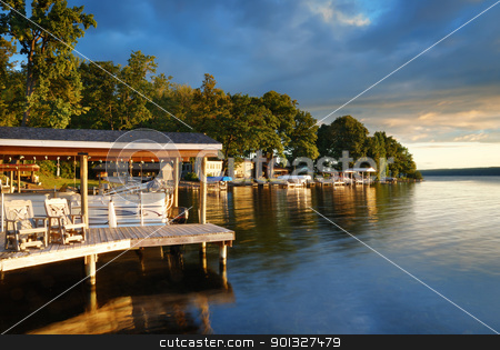 Lake house stock photo, Lake house with pier and woods with sunrise in the morning in New York state Finger Lakes by rabbit75_cut