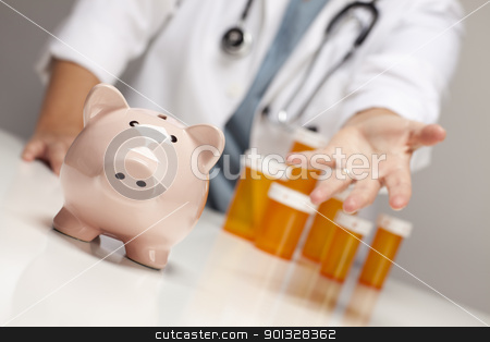 Doctor Reaches Palm Out Behind Medicine Bottles and Piggy Bank stock photo, Doctor Wearing Stethoscope Reaches Palm Out Behind Medicine Bottles and Piggy Bank. by Andy Dean