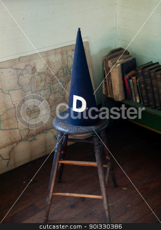 Old dunce cap on stool stock photo, Dunce cap standing on a stool in an old schoolhouse by Steven Heap