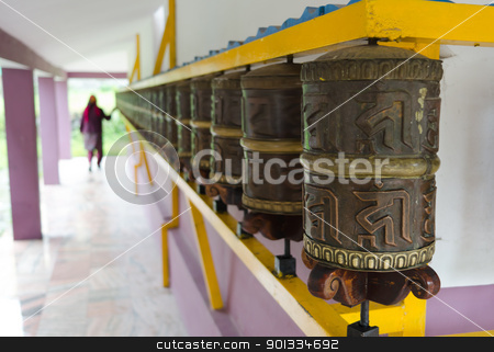 Woman and prayer wheels in a row stock photo, Woman and prayer Buddhism wheels in a row. Focus on the front wheel. by Iryna Rasko