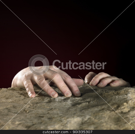 hands on stone surface stock photo, handsclutching on a rough stone in dark back by prill