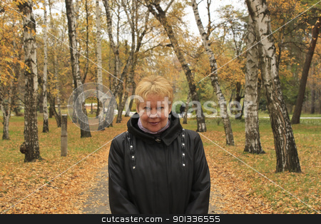 middle-aged woman in autumn park stock photo, Portrait of a middle-aged woman in autumn park by virin
