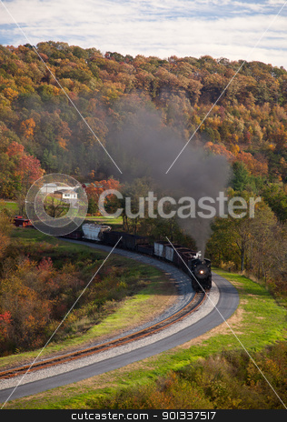 Steam train powers along railway stock photo, Old steam locomotive pulls freight through rural countryside in autumn by Steven Heap