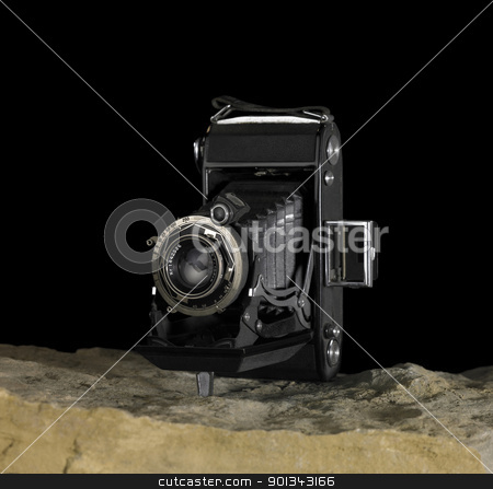 nostalgic camera on stone surface stock photo, Still life with nostalgic camera on stone ground in front of dark back by prill