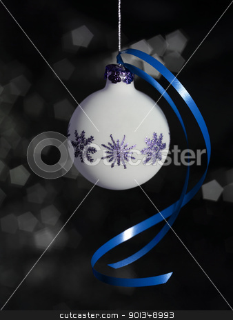 Christmas bauble with blue bow stock photo, white Christmas bauble in dark blurry back by prill