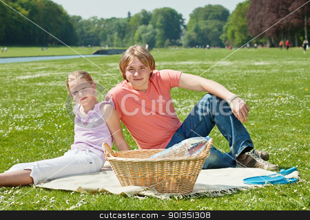 Two teenager siblings at picnic stock photo, Teenager brother and sister enjoying a picnic in the park in a bright sunny day by Mikhail Lavrenov