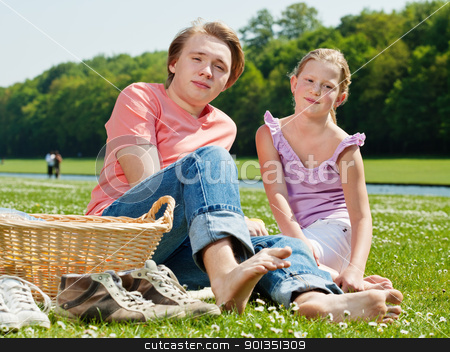 Two teenagers at picnic stock photo, Teenager brother and sister enjoying a picnic in the park in a bright sunny day by Mikhail Lavrenov