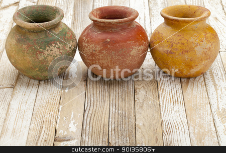 rustic clay pots stock photo, three small  clay plant pots (mass produced planter) with rough, grunge finish,  on white rustic wood background by Marek Uliasz