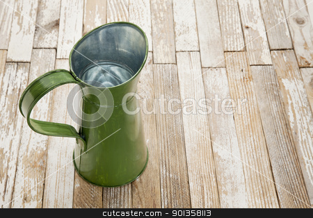 vintage metal water pitcher  stock photo, vintage metal water pitcher against grunge white painted wood table by Marek Uliasz