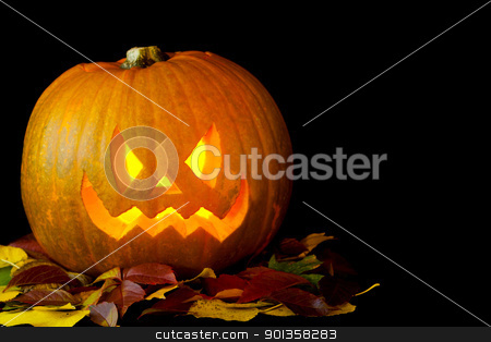 Jack o Lantern stock photo, Carved pumpkin with a candle burning inside and some autumn leaves by mato020